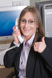 Business woman giving the thumbs up as she has just secured a successful deal,