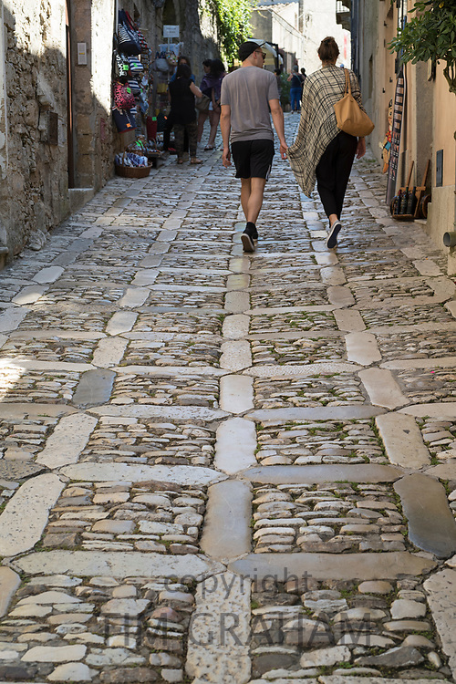 Street scene of back view of young couple in cobble stones alleyway of via Chiesamonte, Erice, Sicily, Italy