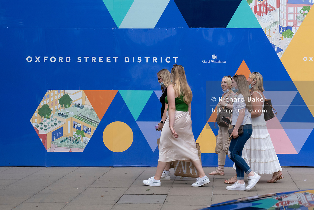 Shoppers walk past a wide billboard promotong retailers along the Oxford Street shopping district, on Covid 'Freedom Day'. This date is what Prime Minister Boris Johnson's UK government has set as the end of strict Covid pandemic social distancing conditions with the end of mandatory face coverings in shops and public transport, on 19th July 2021, in London, England.
