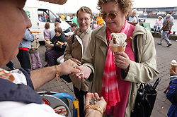 Two elderly women buying an ice cream,
