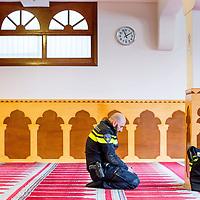 Nederland, Amsterdam, 5 maart 2017.<br /> Op zondag 5 maart om 14.00 uur organiseren het Comité 21 maart en het Collectief Tegen Islamofobie en Discriminatie een solidariteitsbijeenkomst in de Grote Moskee van Amsterdam aan de Weesperzijde 76. Iedereen is uitgenodigd om zijn solidariteit met moslims te tonen. In het huidige politieke klimaat is de rechtsstaat onder druk komen te staan en biedt zij volgens meerdere partijen niet aan alle burgers gelijke bescherming. Daarom zullen we samen een geluid laten horen tegen de haatzaaiende verhalen en met zoveel mogelijk verschillende mensen solidariteit tonen met moslims. Dit is hard nodig omdat zij vaak niet alleen doelwit voor extreem-rechts zijn, maar ook voor religieus extremisme. <br /> De islam en moslims worden vandaag de dag over het hele politieke spectrum geproblematiseerd en dat zorgt voor een gevoel van angst en onveiligheid. Op deze dag komen organisaties die zich inzetten voor de rechten van vrouwen en homo's, tegen anti-zwart racisme en islamofobie, vakbonden en migrantenorganisaties samen om deze angst te vervangen door binding en inclusiviteit. Naast het tonen van solidariteit willen de organisaties iedereen oproepen om naar de stembus te gaan en actief deel te nemen aan het publieke debat. <br /> Gespreksleider is: Yassin El Forkani (Jongerenimam)<br /> Op de foto: Voorafgaand aan de bijeenkomst wordt er gebeden zoals deze Nederlandse politieman van Marokkaanse afkomst.<br />  <br /> <br /> <br /> Foto: Jean-Pierre Jans