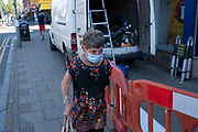 With most shops now open but with retail sales suffering due to the Coronavirus pandemic, shoppers wearing face maks, which became compulsory in shops on the 24th July, go out shopping on Kings Heath High Street on 31st July 2020 in Birmingham, United Kingdom. Coronavirus or Covid-19 is a respiratory illness that has not previously been seen in humans. While much or Europe has been placed into lockdown, the UK government has put in place more stringent rules as part of their long term strategy, and in particular social distancing.