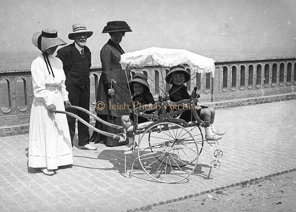 French woman (possibly a nanny), pushing a pram with two children. Circa 1900