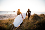Couple with surfboards walking through the sand dunes towards the golden sunlight near Le Rocco Tower at Le Braye, St Ouen's Bay, Jersey, CI