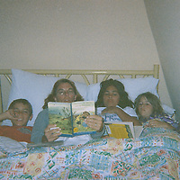 """1. When was this photo taken?<br /> <br /> 2004ish?<br /> <br /> 2. Where was this photo taken?<br /> <br /> Destin, Florida<br /> <br /> 3. Who took this photo?<br /> <br /> Jennifer Mitchell<br /> <br /> 4. What are we looking at here?<br /> <br /> After a day of frolicking on the beach, this is my sister who is reading to her two children and our niece.<br /> <br /> 5. How does this old photo make you feel?<br /> <br /> As all the kiddos in the picture are my nieces and nephew, it makes me feel amazingly proud. One is in the Air Force Academy, one is a wedding planner in a Colorado Rocky Mountain resort, and one just got accepted into a Phd program for Astrophysics. I bet my sister (who is reading to them) thinks that she might have had a little something to do with it. :) When I showed her the picture, she sighed and said, """"Oh, that was always one of my favorite things to do with those kids!""""<br /> <br /> 6. Is this what you expected to see?<br /> <br /> I honestly had no idea what to expect!<br /> <br /> 7. What kind of memories does this photo bring back?<br /> <br /> Whenever possible, our family goes to Destin, Florida. We have for years. And even though this is not a beach picture, it sure reminds me of all those trips we have taken over the years.<br /> <br /> 8. How do you think others will respond to this photo?<br /> <br /> Who doesn't love to be snuggled up and read to? I hope it brings that feeling of security and safety and wrapped around the people that you love."""