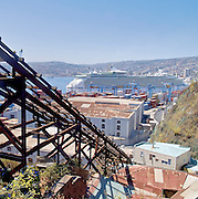 All the typical elements of Valparaiso, a railway of a funicular, the bay with a cruise ship, the hills with houses
