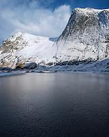 Steep snow covered granite cliffs of Helvetestind mountain rises above ice covered Bunes beach, Moskenesøy, Lofoten Islands, Norway