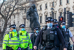 © Licensed to London News Pictures. 06/01/2021. London, UK. Police officers surround Churchill's statue after anti-lockdown protesters descended on Parliament Square in central London with some being arrested as Police get tough on breaking lockdown rules. Yesterday, Prime Minister Boris Johnson plunged England into another lockdown as he ordered schools to close and office workers to work from home in his televised address to the nation. This week, the first person in the world was vaccinated with the Oxford AstraZeneca Covid-19 vaccine with over 500,000 doses made available for high risk groups as the government race to vaccinate 13 million people in seven weeks. Photo credit: Alex Lentati/LNP