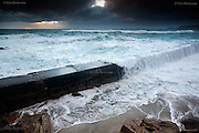 Storm at Sennen Cove, West Penwith, Cornwall, where Atlantic waves broke over the small harbour wall on the South side of the wide bay. Cape Cornwall headland near St Just can be seen in the background.