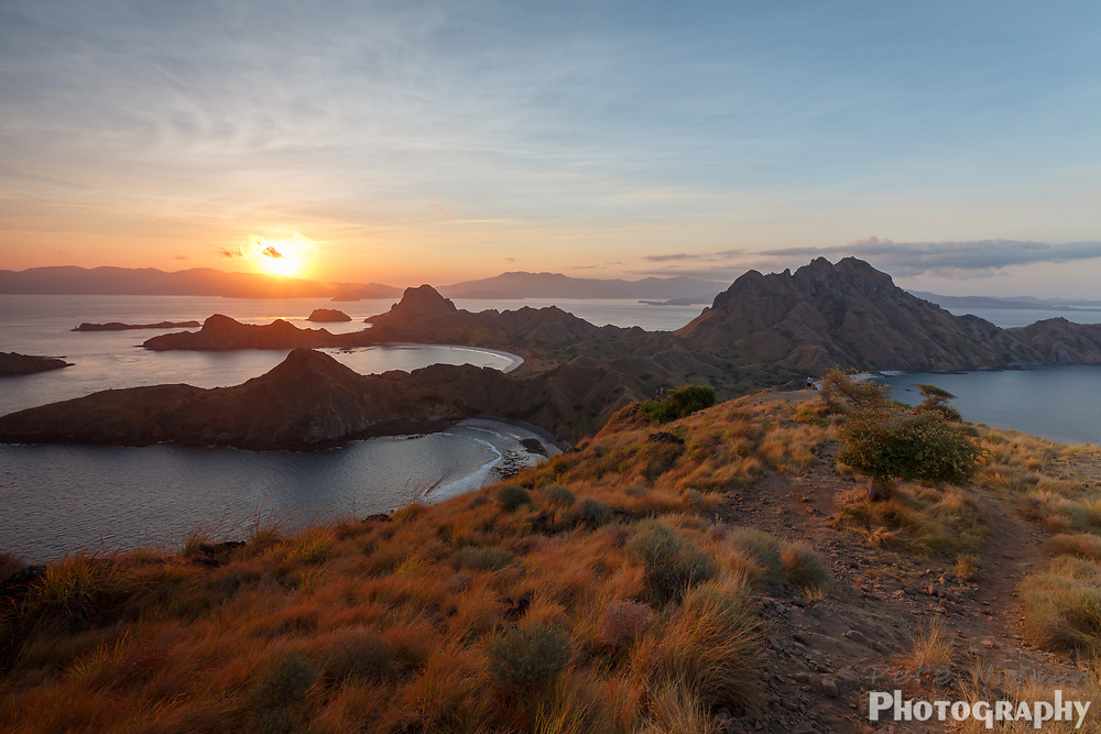 Sunset from hilltop on mountains in Komodo national park silhouettes multiple rock outcrops off shore