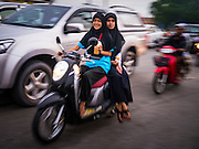 08 JULY 2013 - PATTANI, PATTANI, THAILAND:   A Thai Muslim woman drinks an iced coffee drink on her motorcycle Monday afternoon, the day before Ramadan. Ramadan starts July 9 and Monday was the last day observant Muslims were able to eat and drink during daylight hours. Muslims fast during the holy month of Ramadan, taking breakfast before dawn and not eating again until after sunset. The restaurants in Pattani, a Muslim majority city in southern Thailand, were packed Monday afternoon and evening.  PHOTO BY JACK KURTZ