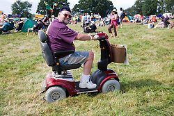 Man driving a motorised mobility scooter across the grass at the Cropredy Festival  Fairport's Cropredy Convention  2005