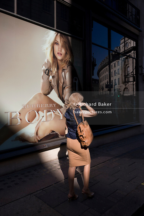 Woman walks past a giant Burberry poster girl ad of the actress Rosie Alice Huntington-Whiteley in central London. It is lunchtime and the woman passes-by with a snack and a coffee, wearing a blue dress and with her long blonde hair trailing in the afternoon breeze. Burberry Group plc is a British luxury fashion house, manufacturing clothing, fragrance, and fashion accessories. Rosie Alice Huntington-Whiteley (born 18 April 1987) is an English model and actress unveiled as the face of Burberry's newest fragrance, Burberry Body, in July 2011 but also best known for her work for Victoria's Secret, Burberry, and her role as Carly Spencer in the 2011 film Transformers: Dark of the Moon, part of the Transformers film series