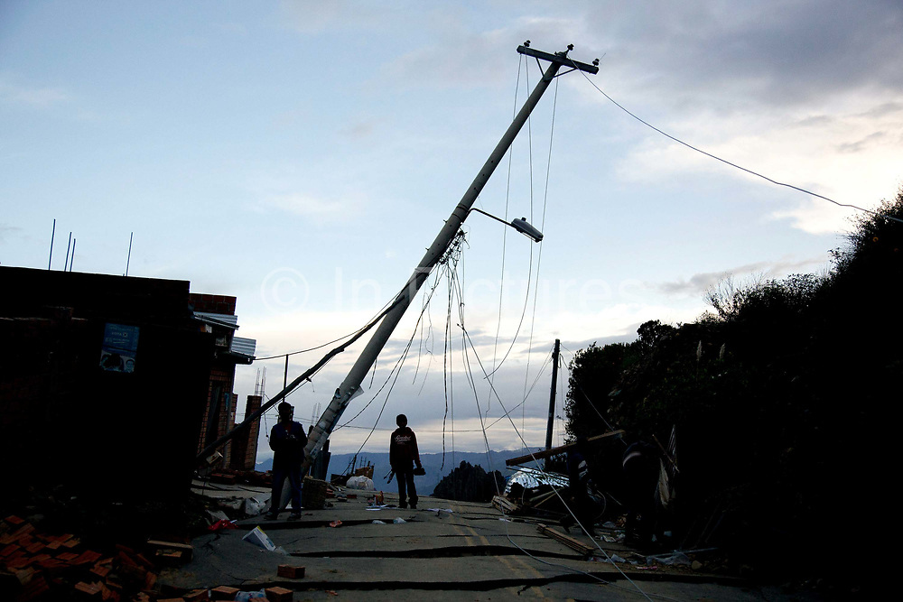 Silhouette of a young boy carrying posessions out of their wrecked home under a bent telegraph pole, after a major lansdlide in La Paz in 2011 made around 25,000 people homeless, due to heavy rain and poor infrastructure, there were no fatalities and only minor injuries sustained