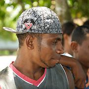 Portrait of a young papua wearing a baseball cap.