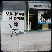 """A broken shop in Alexandras avenue, Athens. The graffiti writes: """"Burn the parliament"""" <br /> <br /> Following the murder of a 15 year old boy, Alexandros Grigoropoulos, by a policeman on 6 December 2008 widespread riots, protests and unrest followed lasting for several weeks and spreading beyond the capital and even overseas<br /> <br /> When I walked in the streets of my town the day after the riots I instantly forgot the image I had about Athens, that of a bustling, peaceful, energetic metropolis and in my mind came the old photographs from WWII, the civil war and the students uprising against the dictatorship. <br /> <br /> Thus I decided not to turn my digital camera straight to the destroyed buildings but to photograph through an old camera that worked as a filter, a barrier between me and the city."""