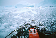 Zodiac Inflatable craft moving through iceflow, icebergs, Antarctic Peninsula, Antarctica