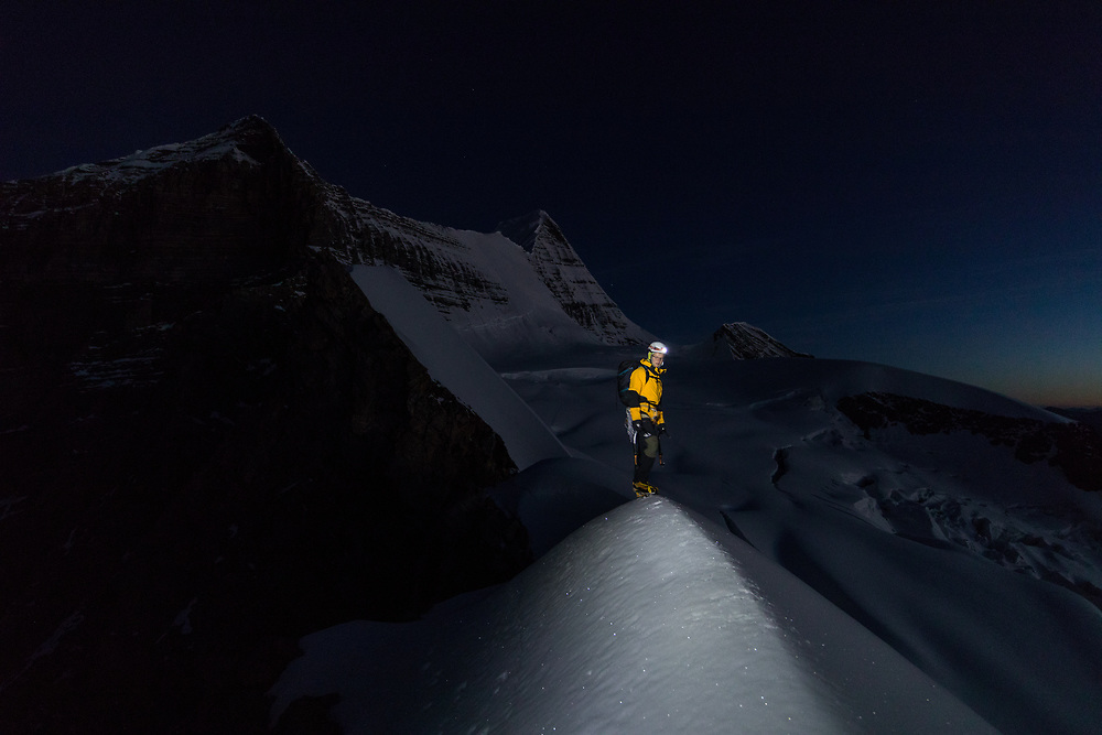 Dane Steadmand at twilight, just before sunrise while climbing Mt Robson in Mt Robson Provincial Park, British Columbia