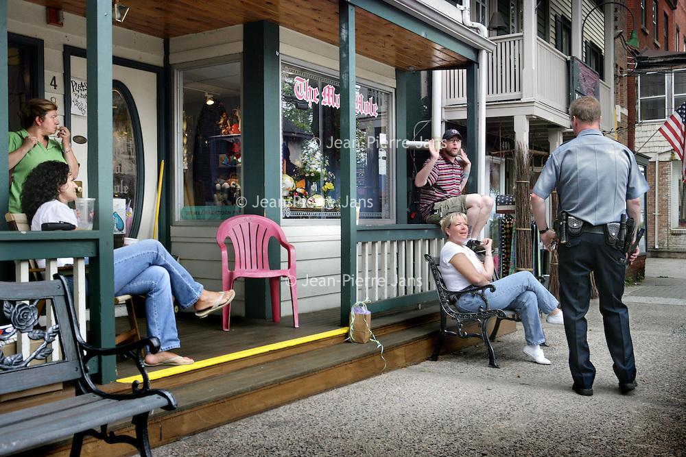 Verenigde Staten.Piermont.New York State.Rockland. 8 juli 2005.<br /> Straatbeeld in het centrum van Piermont, een dorpje aan de rivier de Hudson zo'n 30 km buiten New York city.<br /> Op de foto: agent maakt praatje met buurtbewoners.Politieagent.Autoriteit.Layd Back.Terras.Veranda.Public service.<br /> Archives 2005, in the streets of Piermont, New York USA.