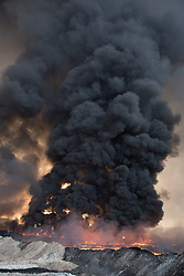 Licensed to London News Pictures. 20/10/2016. Smoke rises from burning oil wells, now on fire for around two months, in the town of Qayyarah, Iraq. The oil wells, located in a residential neighbourhood on the edge of the town, were set alight in July by retreating Islamic State militants as part of a scorched earth policy.<br /> <br /> Since being retaken from the Islamic State the town of Qayyarah has become an important staging post for the Iraqi Army, and some US support elements, in the buildup to the Mosul offensive. Photo credit: Matt Cetti-Roberts/LNP