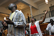 Members of the public invoking the Lord and praying for the Holy Spirit to descend on them during a Mass Service at the Hip Hop Church in Harlem, New York, NY., on Thursday, July 6, 2006. A new growing phenomenon in the United States, and in particular in its most multiethnic city, New York, the Hip Hop Church is the meeting point between Hip Hop and Christianity, a place where ?God? is worshipped not according to religious dogmatisms and rules, but where the ?Holy Spirit? is celebrated by the community through young, unique, passionate Hip Hop lyrics. Its mission is to present the Christian Gospel in a setting that appeals to both, those individuals who are confessed Christians, as well as those who are not regularly attending traditional Services, while helping many youngsters from underprivileged neighbourhoods to feel part of a community, to make them feel loved and to help them not to give up when problems arise. The Hip Hop Church is not only forward-thinking but it also has an important impact where life at times can be difficult and deceiving, and where young people can be easily influenced for the worst purposes. At the Hip Hop Church, members are encouraged to sing, dance and express themselves in any way that the ?Spirit of God? moves them. Honours to students who have overcome adversity, community leaders, church leaders and some of the unsung pioneers of Hip Hop are common at this Church. Here, Hip Hop is the culture, while Jesus is the centre. Services are being mainly in Harlem, where many African Americans live; although the Hip Hop Church is not exclusive and people from any ethnic group are happily accepted and involved with as much enthusiasm. Rev. Ferguson, one of its pioneer founders, has developed ?Hip-Hop Homiletics?, a preaching and worship technique designed to reach the children in their language and highlight their sensibilities, while bringing forth Christianity. This ?Keep It Real? evangelism style is the centrepiece of Rev. Ferguson?s m