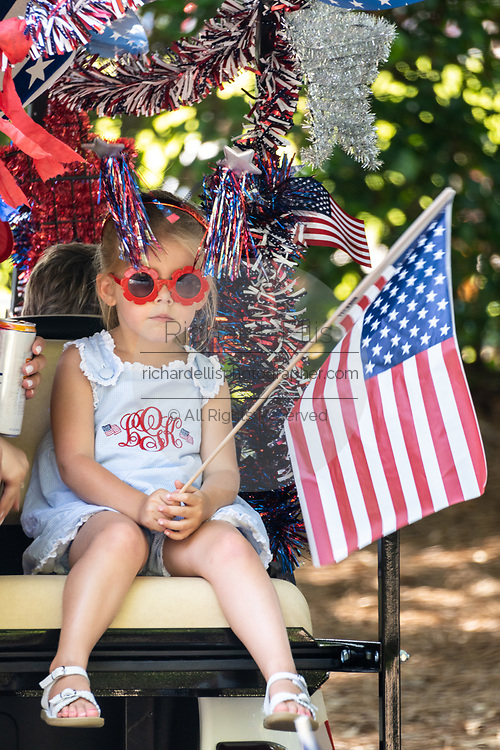 Mount Pleasant, United States of America. 04 July, 2020. Children wave flags during a golf cart  Independence Day parade despite a dramatic rise in COVID-19, coronavirus cases in Charleston County July 4, 2020 in Mount Pleasant, South Carolina. South Carolina is currently number three nationwide in number of infected per population.  Credit: Richard Ellis/Alamy Live News