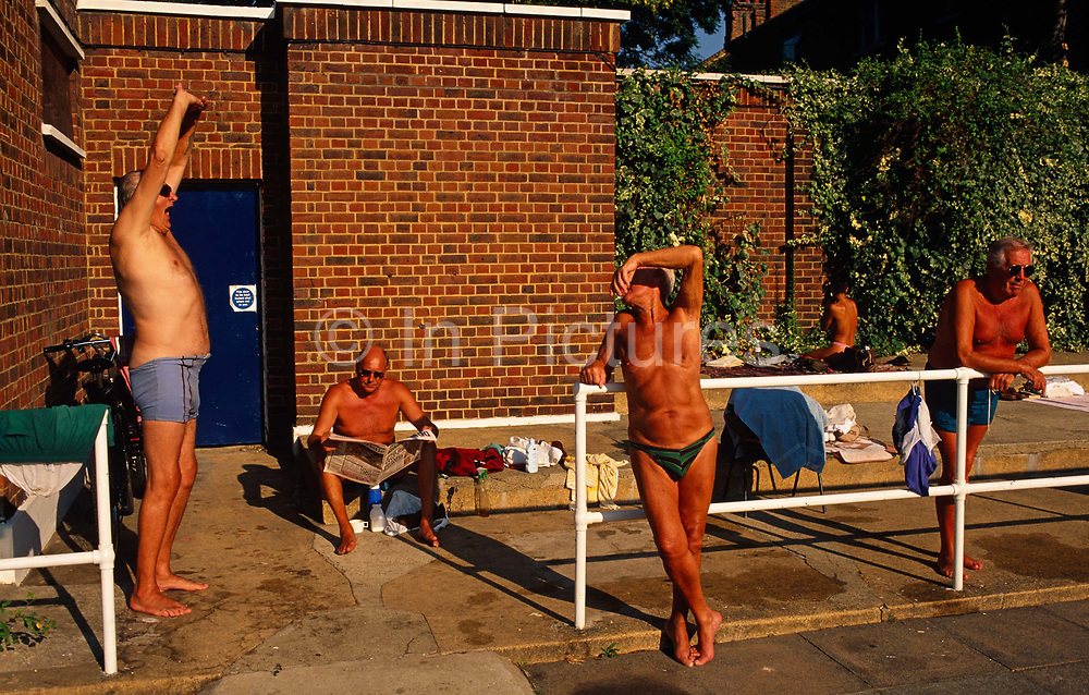 Four friends gather every morning in the summer at Brockwell (Brixton) Lido. This is a favourite place in the capital for varied groups of people  to meet, swim or just hang out like these London taxi drivers who regularly meet for exercise sessions, accumulating sun tans during long periods in the sunshine. Bare except for their costumes, they stretch and yawn, read a newspaper and lean against a railing all the while swapping anecdotes and complaining grumpily about the state of the world near a brick wall that retains heat. Brockwell Lido in Herne Hill SE24 was originally built in 1937 at a time of coastal and city pool-building but went into decline when bathers preferred to holiday in warmer Spain. Its revival happened when local entrepreneurs re-opened the business and it now enjoys a reputation for some of the best urban swims in the UK.