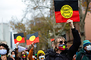 A woman wearing a facemask in the colours of the Aboriginal flag, stands in solidarity against police brutality during a Black Lives Mater rally on 06 June, 2020 in Melbourne, Australia. This event was organised to rally against aboriginal deaths in custody in Australia as well as in unity with protests across the United States following the killing of an unarmed black man George Floyd at the hands of a police officer in Minneapolis, Minnesota. (Photo by Dave Hewison/ Speed Media)