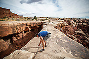 SHOT 10/17/16 10:35:01 AM - Mike Tryggestad of Denver, Co.spreads the ashes of friend Doug Pensinger atop Musselman Arch on the White Rim Trail. The White Rim is a mountain biking trip in Canyonlands National Park just outside of Moab, Utah. The White Rim Road is a 71.2-mile-long unpaved four-wheel drive road that traverses the top of the White Rim Sandstone formation below the Island in the Sky mesa of Canyonlands National Park in southern Utah in the United States. The road was constructed in the 1950s by the Atomic Energy Commission to provide access for individual prospectors intent on mining uranium deposits for use in nuclear weapons production during the Cold War. Four-wheel drive vehicles and mountain bikes are the most common modes of transport though horseback riding and hiking are also permitted.<br /> (Photo by Marc Piscotty / © 2016)