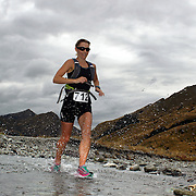 Runner Rachael Buttart crosses Moke Creek on the Ben Lomond High Country Station during the Pure South Shotover Moonlight Mountain Marathon and trail runs. Moke Lake, Queenstown, New Zealand. 4th February 2012. Photo Tim Clayton