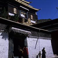 CHINA, TIBET.  Tibetan Buddhist devotees enter gompa (temple) at Tashilumpo Monastery in Shigatse, home of Panchen Lama, 2nd holiest in Tibet