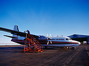 Pacific Alaska Airlines Fokker F27 being fueled at the POW-Main Dew Line Station at Point Barrow, corrugated steel tarmac covers Arctic Ocean beach sand, Alaska.