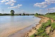 Nederland, Gennep, 20-5-2018Bij Gennep wordt het talud van de brug, verkeersbrug naar oeffelt, uitgegraven en vervangen door pijlers zodat het bij hoogwater beter doorstroomt. Dit talud vormt dan een flessenhals, obstakel voor het doorstromen . De Maasoevers moeten volgens RWS vrij zijn van obstakels en dus worden de bakenbomen niet meer vervangen . Deze bakenbomen op de oever zijn karakteristiek voor het landschap langs de rivier de Maas . De Maas krijgt de ruimte. Door de aanleg van natuurvriendelijke oevers ontstaat er een geleidelijke overgang van water naar land. Op veel plaatsen langs de meanderende maas zijn nevengeulen aangelegd om het water meer ruimte te geven .Foto: Flip Franssen