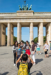 Asian tour group posting for photograph in front of Brandenburg Gate in Mitte district of Berlin Germany
