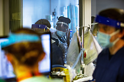 © Licensed to London News Pictures . 12/02/2021 .  Manchester , UK . Clinicians are seen through a window working on Ward 4 , the Respiratory Cohort Area . Inside Manchester Royal Infirmary , where patients are being treated for the effects of Coronavirus . Photo credit : Joel Goodman/LNP