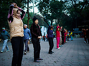 26 DECEMBER 2017 - HANOI, VIETNAM: People gather for an aerobics session at Hoan Kiem Lake, in the Old Quarter of Hanoi. Thousands of Vietnamese people line the lake front in the early hours of the morning to perform tai chi and other low impact aerobic workouts.     PHOTO BY JACK KURTZ