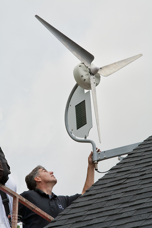"""Installation of a residential wind turbine is filmed for an episode of the DIY network show """"This New House"""". Bob Hayes of Sustainable Winds and his crew install a Dyocore SolAir 800 I wind turbine which integrates two small solar panels into its design and is capable of producing up to 800 Watts at 12 mph. The two solar panels produce up to 45watts. Redondo Beach, Ca, USA"""