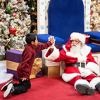 Ramone Montelongo, gives Santa Claus a high five, Sunday Dec. 9 at Rio West Mall during their Santa Cares event. The Rio West Mall partnered with Autism Speaks to host a Santa event for kids with special needs.