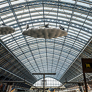 Looking straight down the Eurostar platforms under the distinctive iron and glass arched cover over the platforms of St Pancras Railway Station (now known as St Pancras International). The renovated station features distinctive Victorian architecture and serves as a Eurostar terminal for high-speed trains to Europe. There are also platforms for domestic train services. The distinctive train shed roof was designed by William Henry Barlow.