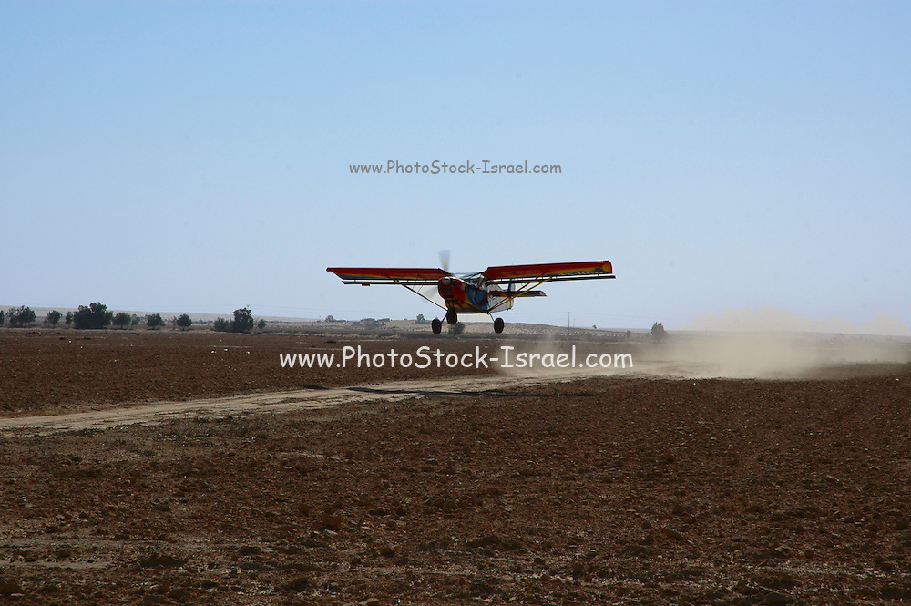 An airplane spraying insecticide over crops;