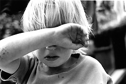 Young child shielding face with arm,