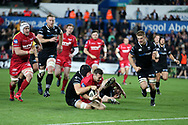 Gareth Davies of the Scarlets © on his way to scoring his teams 1st try in 2nd half.  Guinness Pro14 rugby match, Ospreys v Scarlets at the Liberty Stadium in Swansea, South Wales on Saturday October 7th 2017. <br /> pic by Andrew Orchard, Andrew Orchard sports photography.