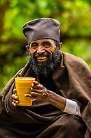 A monk drinks homemade beer outside the Yemrehana Krestos Church, which is an 11th / 12th-century Ethiopian Orthodox church located in Amhara Region, northern Ethiopia. Built of stone and wood, it was erected in the architectural tradition of the ancient Kingdom of Aksum. Located 12 miles northeast from Lalibela, the church was built in a large northeast-facing cave on the west side of Mount Abuna Yosef.