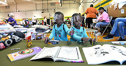 Twin sisters Zahniya, left, and Ahniya Blount, 3, work on coloring books at the Red Cross Shelter at the Carver Heights Elementary School on October 12, 2016 in Goldsboro, NC, USA. Their family left their home as it was flooding on Saturday morning. Photo by Chuck Liddy/Raleigh News & Observer/TNS/ABACAPRESS.COM