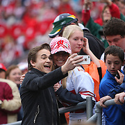 """Country singer Hunter Hayes takes a """"selfie"""" with a Wisconsin fan after his halftime performance at the NCAA Capital One Bowl football game between the South Carolina Gamecocks and the Wisconsin Badgers at the Florida Citrus Bowl on Wednesday, January 1, 2014 in Orlando, Florida. (AP Photo/Alex Menendez)"""