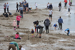 """© Licensed to London News Pictures. 30/08/2014<br /> Folkestone Gold Beach.  5.30pm tide going out.<br /> £10,000 of buried treasure at Outer Harbour beach near Sunny Sands, Folkestone,Kent.<br /> The installation, entitled """"Folkestone Digs"""", is funded by Bristol-based designers Situations and the idea for the project came from Berlin-based artist Michael Sailstorfer.<br /> The small gold bars - similar to a dog tag - come in two sizes, worth around £250 and £500.<br /> <br /> (Byline:Grant Falvey/LNP)"""