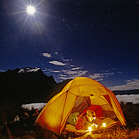 Cordillera Vilcabamba, Peru. Ben Wiltsie sleeps in a tent under the full moon atop Cerro Victoria. In background are Cerro Corihuayrachina and low fog in canyons below.