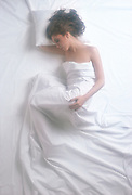 Soft focus overhead view of sleeping woman in bed under the sheets
