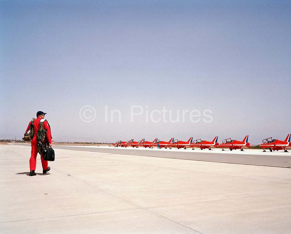 In the mid-day heat, Squadron Leader John Green is a member of the elite 'Red Arrows', Britain's prestigious Royal Air Force aerobatic team. Here he walks out alone to his aircraft, which is lined up with some of the others jets at RAF Akrotiri, Cyprus before flying out to Marka in Jordan for the first display of the year. The Red Arrows arrive each April to fine-tune their air show skills in the clear Mediterranean skies and continue their busy display calendar above the skies of the UK and other European show circuit. We see John Green carrying his flight bag and life-vest over his shoulder. He paces confidently across the bright 'apron' dressed in his famous red flying suit that the Red Arrows have made famous since 1965. He is alone and striding confidently towards the matching red eight Hawk airplanes.