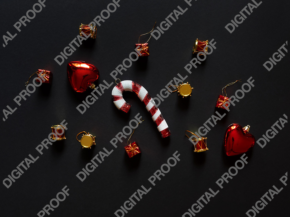Christmas candy cane drums hearts and gifts at studio above view over a black background isolated flatlay